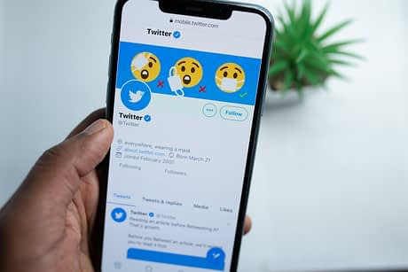 An image of a person using Twitter on their phone